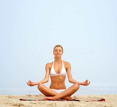Sexy young woman practicing yoga at the beach