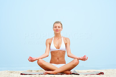 Beautiful young woman practicing yoga at the beach