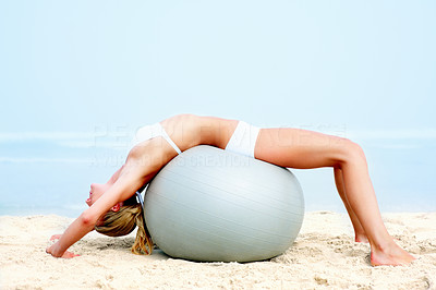 Young woman working out on a fitness ball on the beach