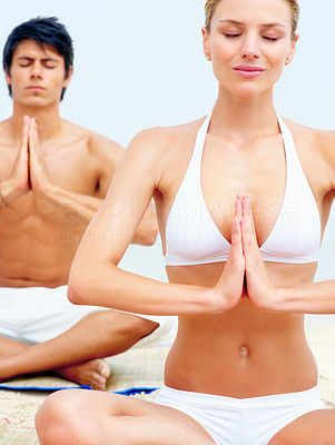 Happy young woman practicing yoga at the beach with a man at the back