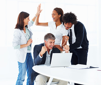 Team of excited business people working together on a laptop