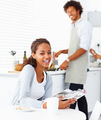 Happy young woman with her husband preparing food at the back