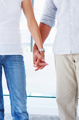Mid section image of a romantic couple holding their hands together