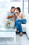 Mature couple sitting on a couch and drinking a glass of wine