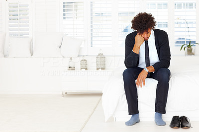 Upset young business man sitting on a bed with his head down