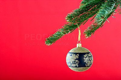 Buy stock photo Cropped detail image of a christmas decoration hanging from the branch of a tree, isolated on red - copyspace