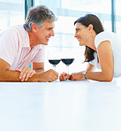 Cute mature couple lying down on the floor at home and having a glass of wine