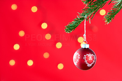 Buy stock photo Christmas decoration hanging from a branch against red background with scattered light effect - copyspace