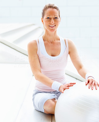 Happy fit mature female sitting besides a fitness ball
