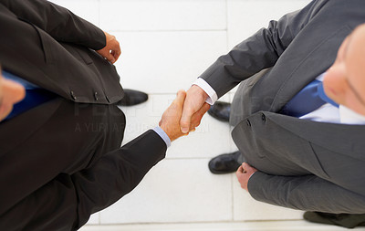 Buy stock photo High angle shot of two businessmen shaking hands