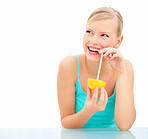 Portrait of laughing young female sipping juice from an orange against white background