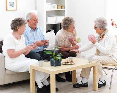 Group of mature people enjoying a game of cards