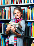Young smiling lady holding books in library