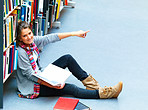 Young pretty lady sitting in the library pointing at something