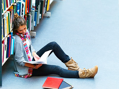 Female student sitting by bookshelf with books in the library