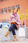 Young happy girl sitting with books in campus