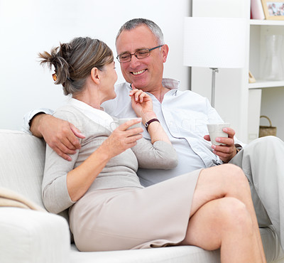 Loving older couple sitting together on couch