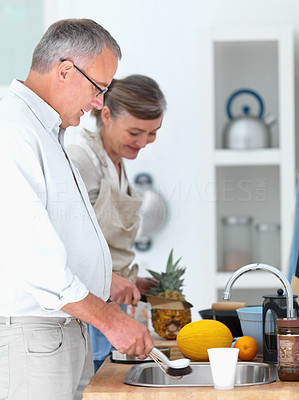 Old mature couple preparing food in the kitchen