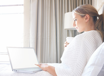 Happy lady sitting on bed and using laptop