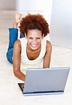 Smiling woman on floor with laptop
