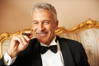 Buy stock photo Closeup of classy gentleman smiling handsomely while smoking a cigar on a piece of antique furniture