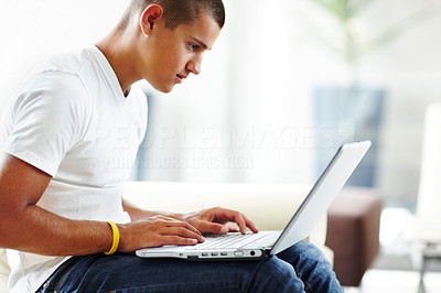 Buy stock photo A handsome young man using a laptop at home to catch up on his studies