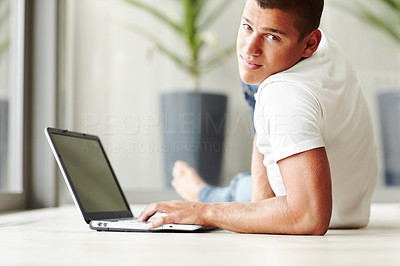 Buy stock photo Smart young guy lying on floor and using laptop