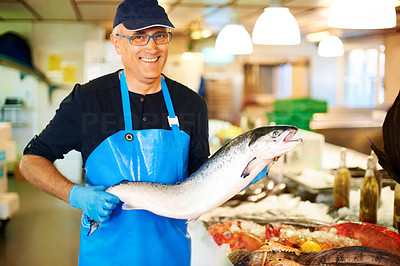 Happy man holding fresh dead fish in his store