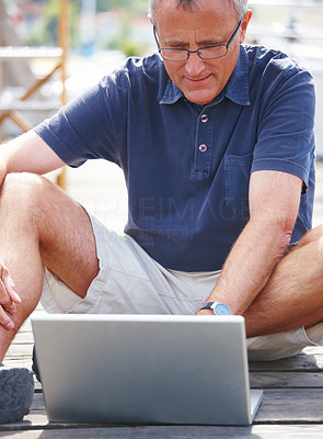 Happy old man sitting on quay using laptop