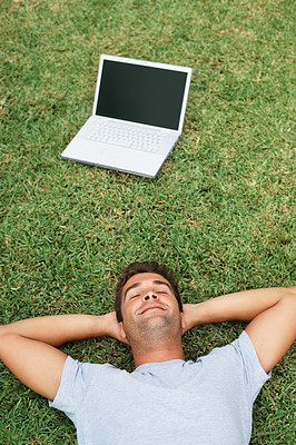 Buy stock photo Handsome man laying on the grass near laptop