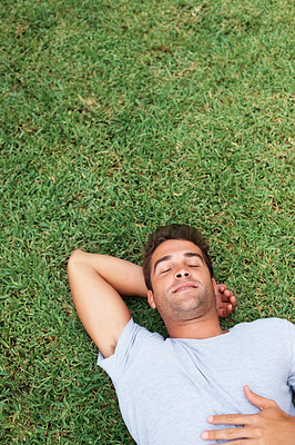 Buy stock photo Handsome man laying on the grass with eyes closed