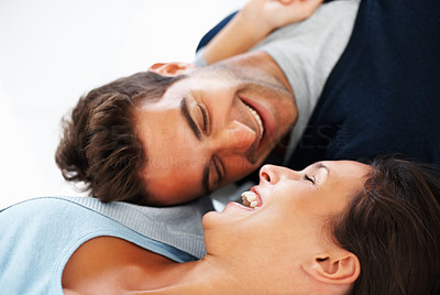 Buy stock photo Attractive couple lying on floor laughing
