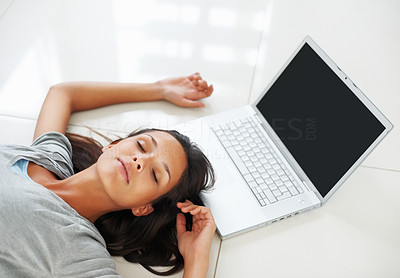 Buy stock photo Pretty woman lying on the floor near laptop with eyes closed