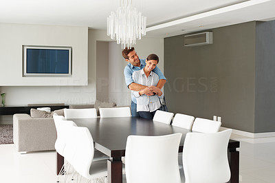 Buy stock photo Affectionate couple embracing in their modern dining room