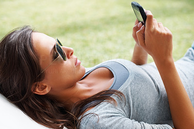 Buy stock photo Pretty woman lying down and looking at a Smartphone