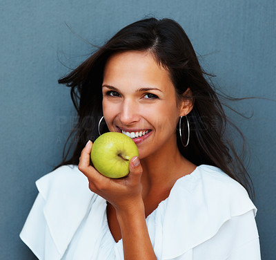 Buy stock photo Head shot of woman holding apple against blue background
