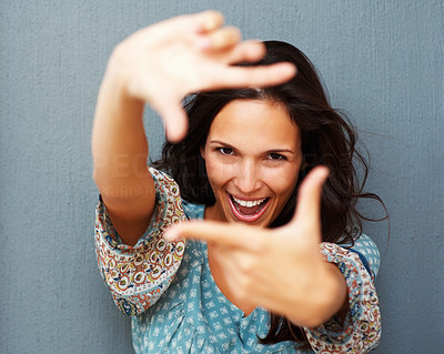 Buy stock photo Smiling woman against blue background making a frame with fingers