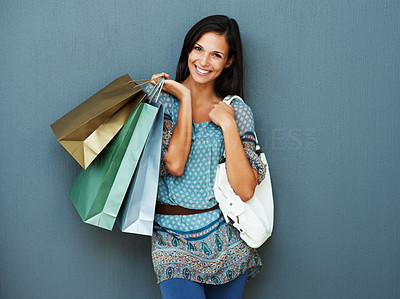 Buy stock photo Pretty young woman holding shopping bags against a blue background with a smile
