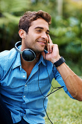 Buy stock photo Shot of a happy young man listening to music on headphones in the park