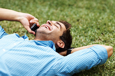 Buy stock photo Shot of a happy young man lying on the grass while talking on the phone