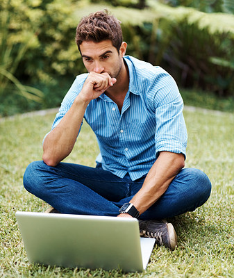 Buy stock photo Shot of a young man working on laptop in a park