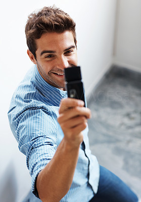 Buy stock photo Shot of a handsome young man taking a picture with a mobile phone