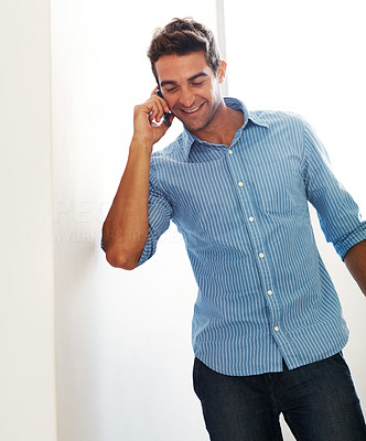 Buy stock photo Shot of a happy young man talking on a cellphone