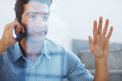 Buy stock photo Shot of a young man looking away while talking on mobile phone behind a glass window
