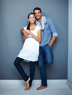 Buy stock photo Portrait of a happy young couple standing together against a grey wall