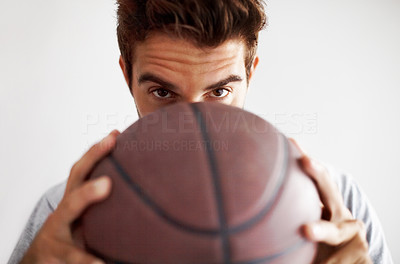 Buy stock photo Studio portrait of a handsome young male holding a basket ball