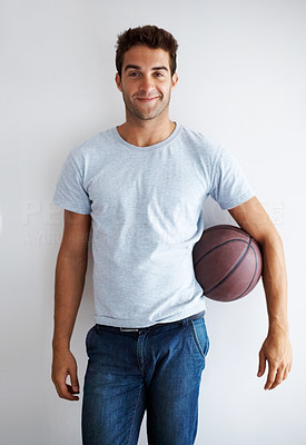 Buy stock photo Studio shot of a handsome young man holding a basketball
