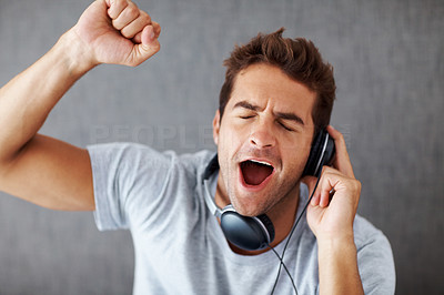 Buy stock photo Portrait of an excited young man listening to music on headphone against grey background