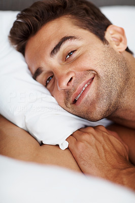 Buy stock photo Shot of a thoughtful young man relaxing in bed at home