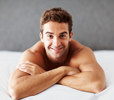 Buy stock photo Portrait of a shirtless young man lying on a bed at home